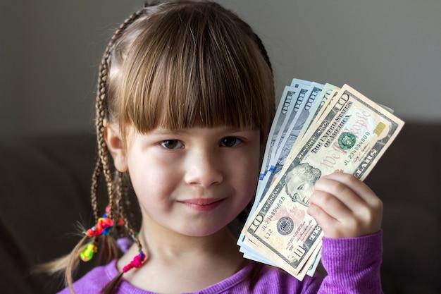 Geld, finanzen und leutekonzept - lächelndes kleines mädchen mit dollarbargeld.
