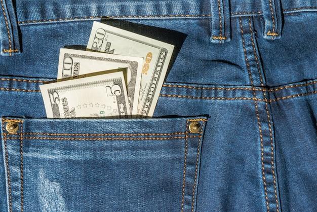 Geld im blue jeans pocket-dollar-bargeldkonzept