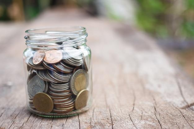 Geld im glasgefäß auf hölzerner tabelle. geld sparen konzept