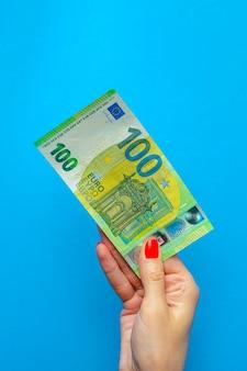 Geld in der hand, banknote in der hand. hand, die 100-euro-banknote auf blauem hintergrund hält.