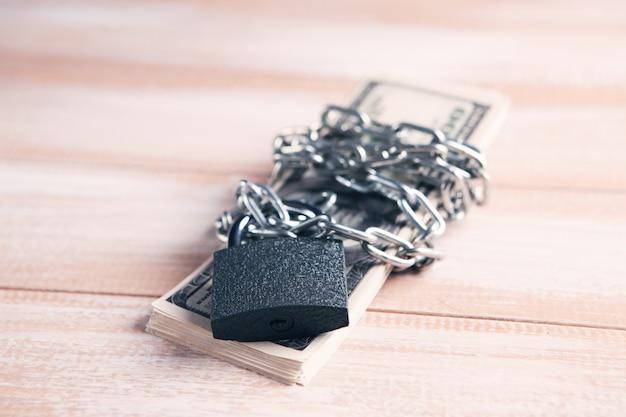 Geld in eine kette gewickelt und mit einem vorhängeschloss verschlossen