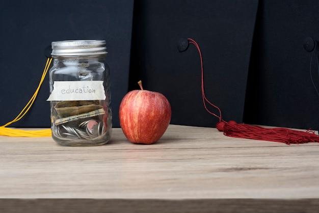 Geld in einem glasgefäß legte auf den tisch für hochschulstudium.