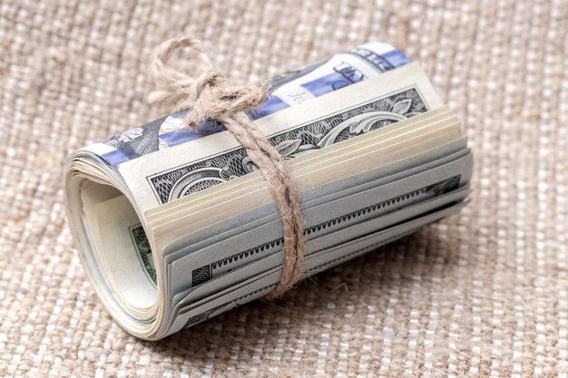 Geld in einer rolle, die mit einem seil gebunden ist, auf sackleinen, us-dollar in einer rolle