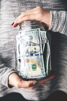 Geld in gläsern in den händen der frauen mit einer schönen maniküre und einem modernen pullover. geschäftsvorschlag.