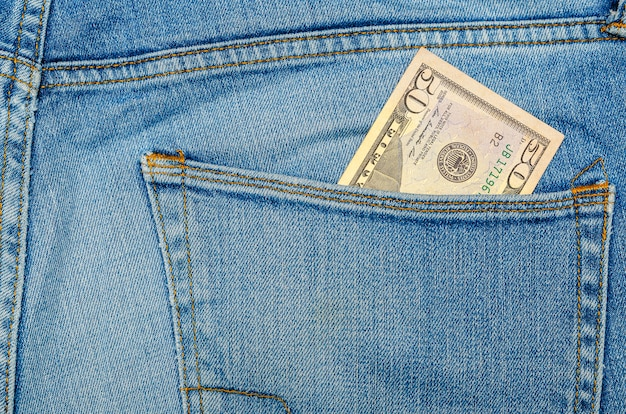 Geld in meiner jeanstasche, fünfzig dollar in der gesäßtasche meiner bluejeans. reichtum und wohlstand konzept. platz für text. platz kopieren