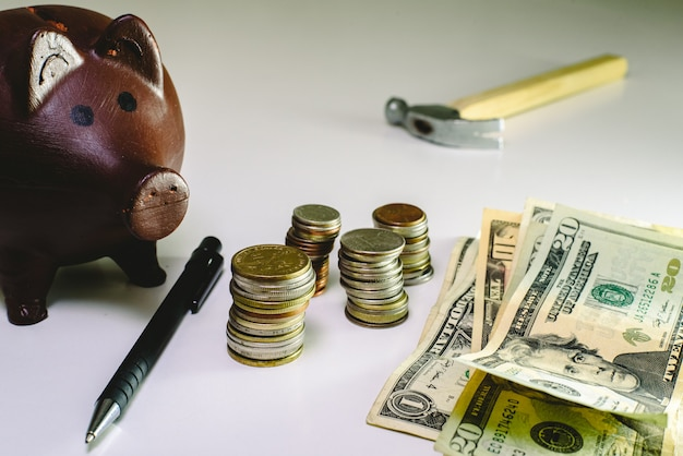 Geld in münzen und rechnungen neben einem sparschwein zu sparen
