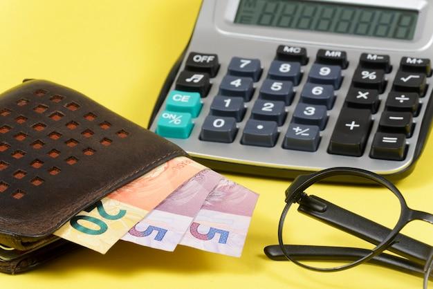 Geld kommt aus der brieftasche mit verschwommenem taschenrechner