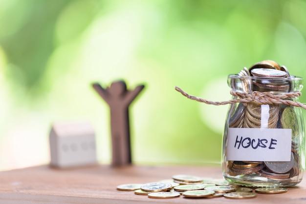 Geld sparen für haus, münzen im glas mit zitat haus auf holztisch
