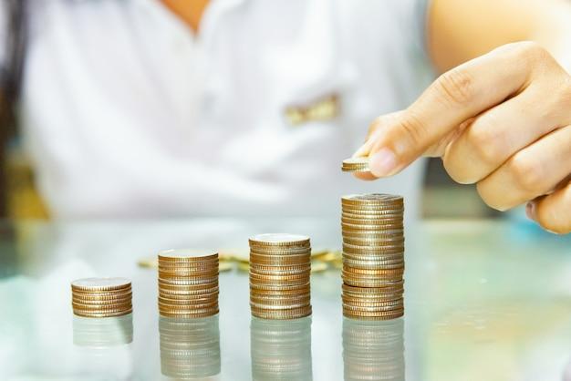 Geld sparen, geldkonzept sparen, frauengriff, der münzen in zunehmende spalten stapelt.