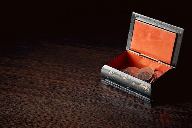 Geld sparen, geschäftskonzept. münzen auf dem tisch neben der kiste.