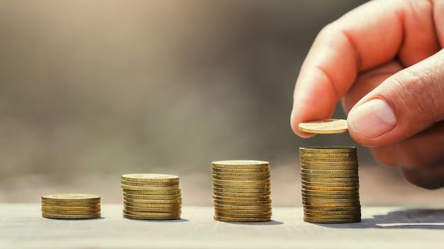 Geld sparen hand, die münzen auf stapel auf tisch mit sonnenschein legt