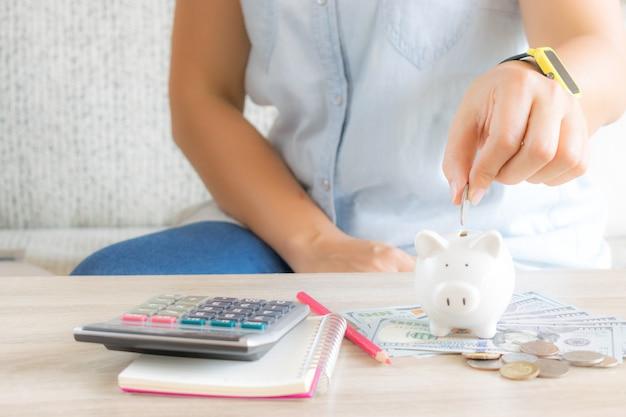 Geld sparen konzept. frauenhand, die bei tisch münze in sparschwein setzt.