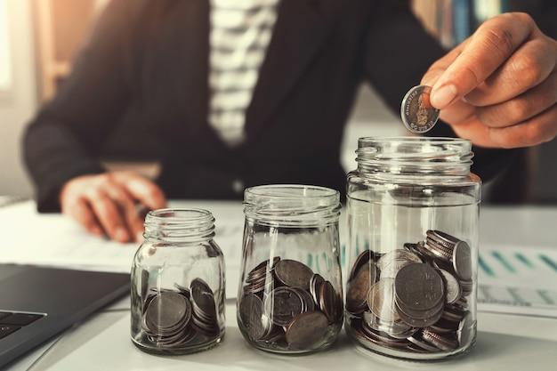Geld sparen mit der hand, die münzen in krugglaskonzept finanziell setzt