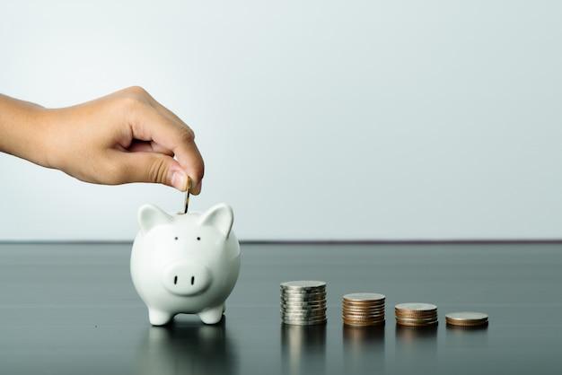 Geld sparen und spendenkonzept, kind legte geld auf niedlichen weißen sparschwein