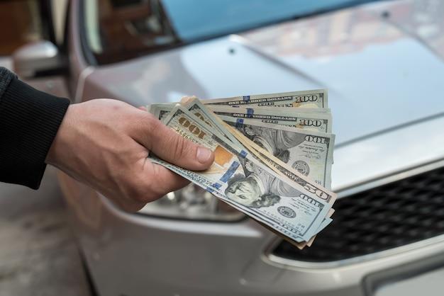 Geld, um das neue auto zu kaufen. finanzkonzept. dollar in der hand