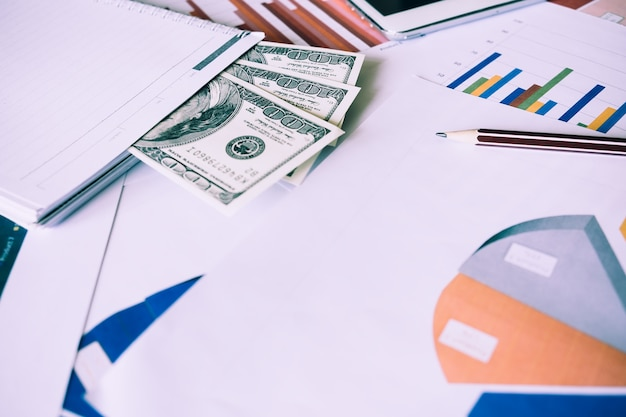 Geld und bleistift mit vielen diagrammen und diagrammen. reflexionslicht und aufflackern