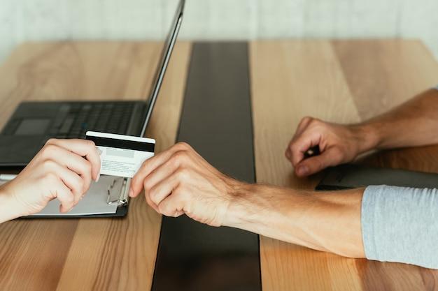 Geld und finanzen. elektronische zahlung. kredite und kredite. zwei personen mit kredit- oder debitbankkarte. finanzgeschäfte online.