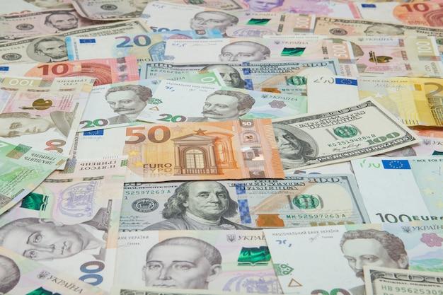 Geld und finanzen. hundert dollar neue rechnung auf buntem auszug der ukrainischen, amerikanischen und nationalen eurowährungsbanknoten