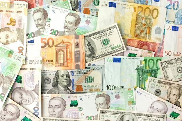 Geld und finanzen-konzept. hundert dollar neue rechnung auf buntem abstraktem hintergrund der ukrainischen, amerikanischen und nationalen eurobanknoten