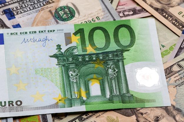 Geld und finanzen-konzept. hundert neue eurorechnung auf buntem abstraktem hintergrund der amerikanischen landeswährung, dollarbanknoten.