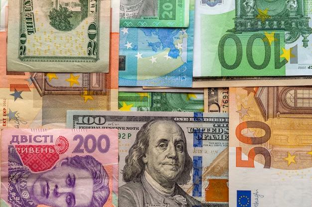Geld- und finanzkonzept. einhundert dollar neuer schein auf bunter zusammenfassung der banknoten der ukrainischen, amerikanischen und euro-landeswährung.