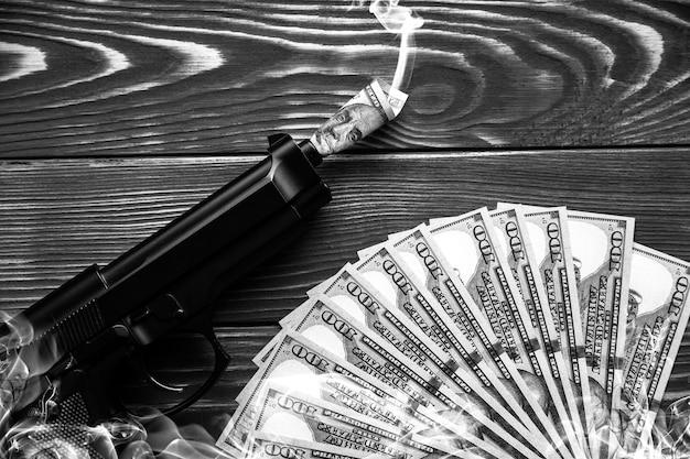Geld und gewehr, die auf hölzernem hintergrund liegen. dollar regieren die welt. verderbte welt. gier töten. rauch um das bild.