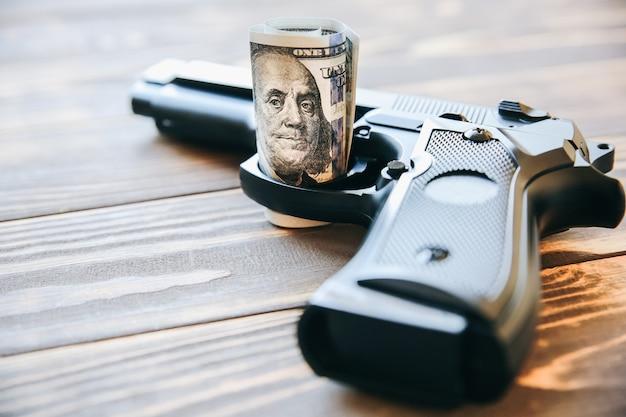 Geld und gewehr, die auf hölzernem hintergrund liegen. dollar regieren die welt. verderbte welt. gier töten.