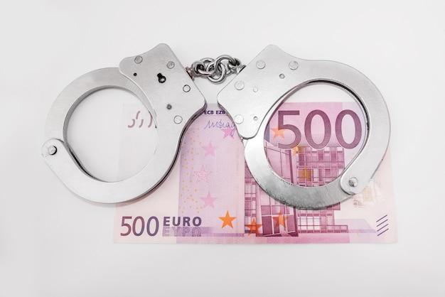 Geld und handschellen. das konzept von korruption, betrug, geldwäsche. 500 euro und graue handschellen auf weißem grund.