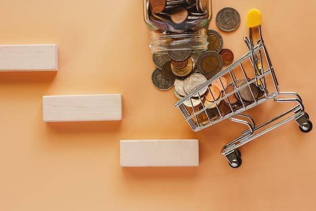 Geld und münzen bilden glasgefäß zum minieinkaufswagen oder laufkatze mit hölzernem spielzeugtreppenhaus