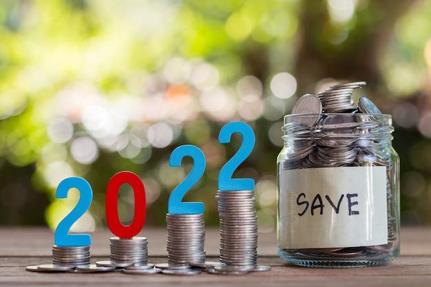 Geld und münzen in einer glasflasche auf einem holzboden sparen. anlagekonzept für die zukunft. mit bokeh hintergrund