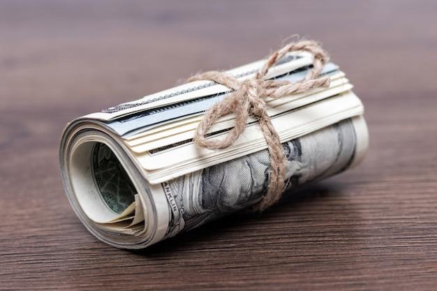 Geld (us-dollar) in einer rolle, die mit einem seil auf einem dunklen hölzernen hintergrund gebunden wird
