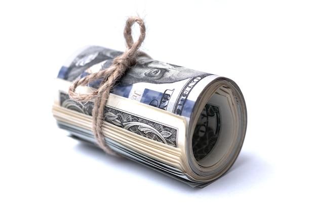 Geld (us-dollar) in einer rolle, die mit einem seil auf einem weißen isolierten hintergrund gebunden wird