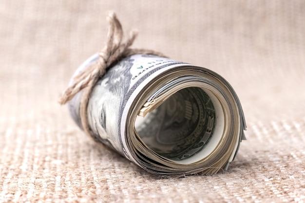 Geld (us-dollar) in einer rolle, die mit einem seil auf sackleinen gebunden ist