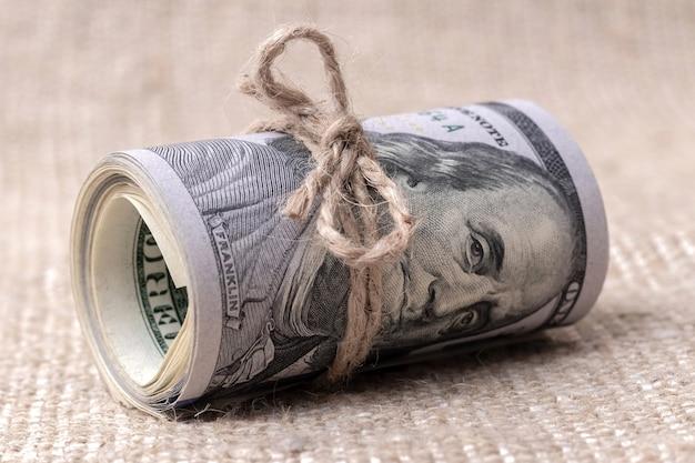 Geld (us-dollar) in einer rolle, die mit einem seil gebunden ist Premium Fotos