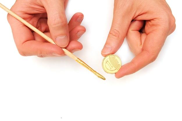 Geld verdienen. goldmünzen und ein pinsel mit farbe in männlichen händen lokalisiert auf weiß