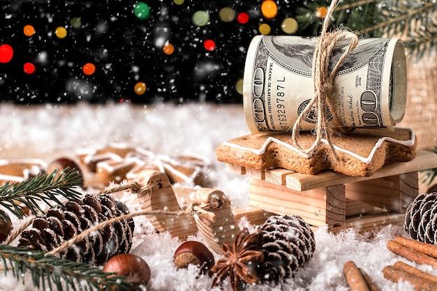 Geld-weihnachtsgeschenk mit hölzernem schlitten. weihnachtskonzept