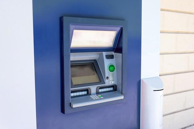 Geldautomat in der wand eines gebäudes in einer stadtstraße, in betrieb und funktionsfähig, keine menschen in der nähe.