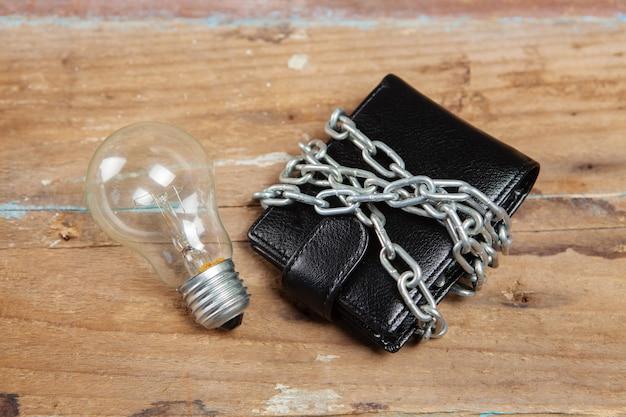 Geldbörse in ketten und eine glühbirne auf dem tisch