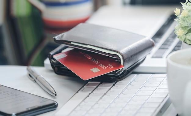 Geldbörse mit kreditkarte auf weißer tastatur.