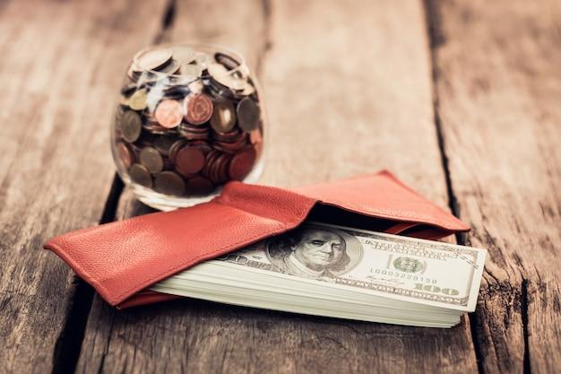 Geldbörse mit us-dollars auf hölzerner tabelle, geld mit lederner orange geldbörse