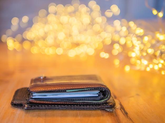 Geldbörse und bewegliches abdeckungsleder auf holztisch mit kleinem verzierendem hellem bokeh hintergrund