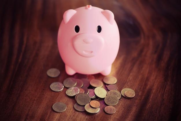 Geldmünze und rosa sparschwein am tisch zu hause schließen oben. sparen sie geld für das stipendienkonzept