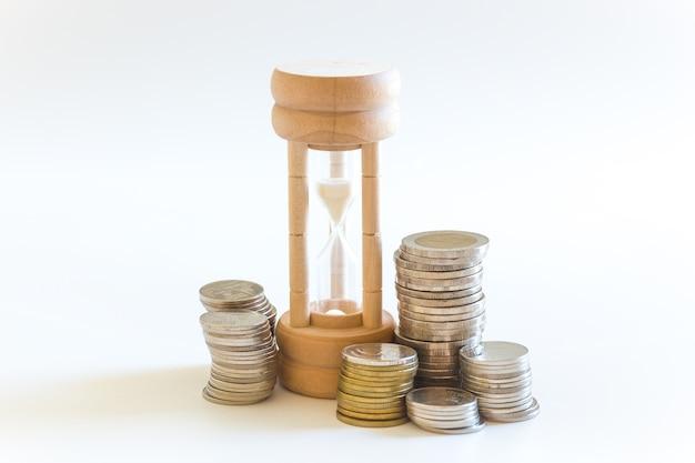 Geldmünze und sanduhr für das geschäftseinkommenszeit- und -finanzkonzept
