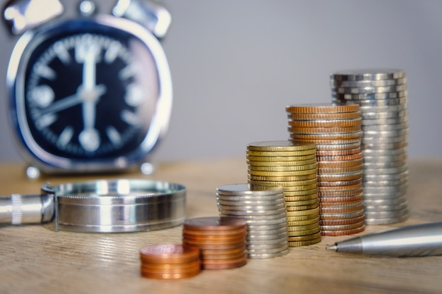 Geldmünzen, die mit uhr- und vergrößerungsglasglas für das spar- und investitionskonzept stapeln.