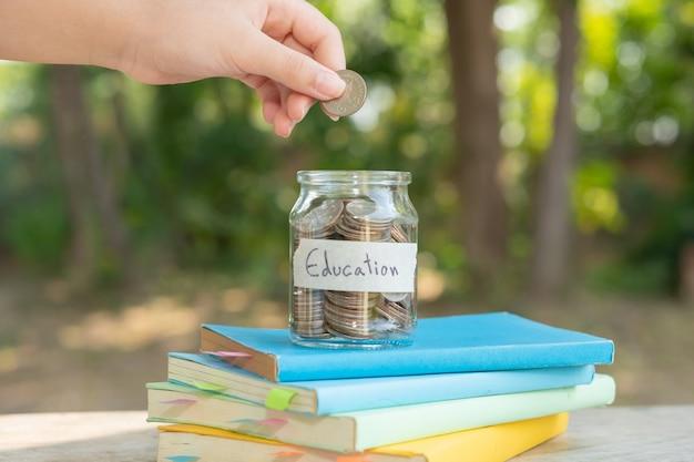 Geldmünzen sparen in glasflasche für konzeptinvestitionsfondsfinanzierung und -geschäft, platziert auf dem lehrbuch. inhalt geld sparen für bildung.