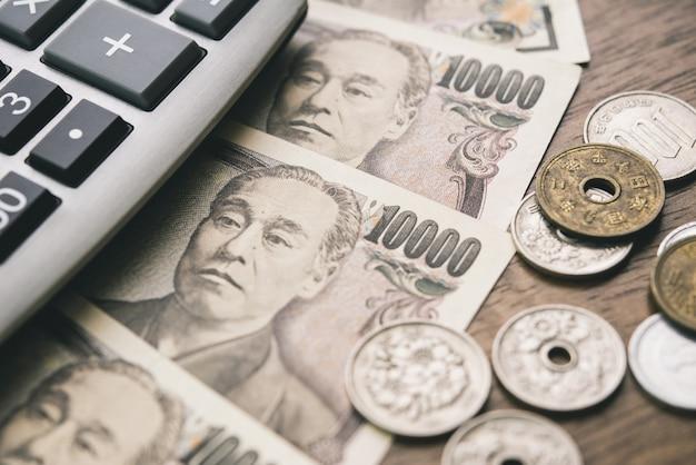 Geldscheine und münzen der japanischen yen mit taschenrechner auf dem tisch