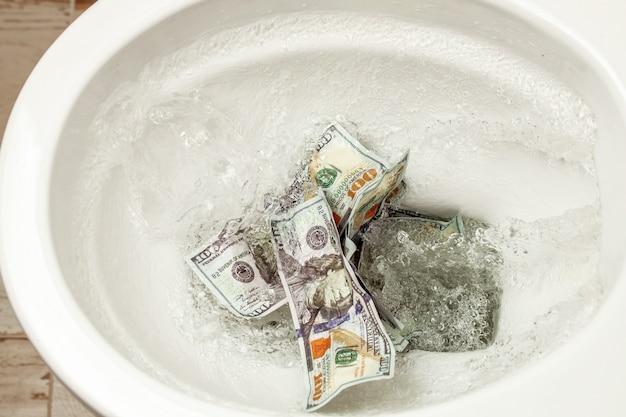 Geldverlust. fehlinvestition oder investition. gelddollar werden in die toilette gespült.