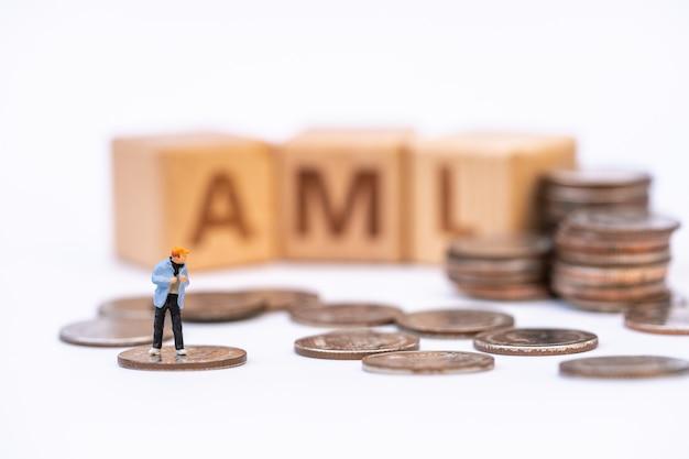 Geldwäsche-konzept. miniaturmenschen, finanzverbrecher auf haufen münzen und hölzerner wortblock