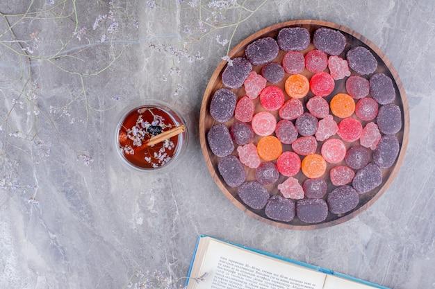 Geleesüßigkeiten in einem holzteller mit einer tasse kräutertee