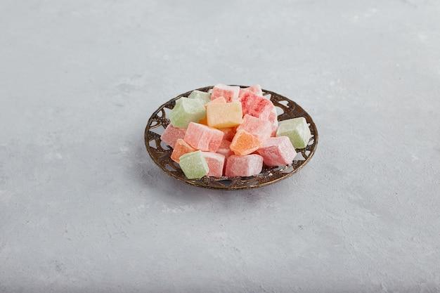 Geleesüßigkeiten werden in einer metallischen untertasse serviert.